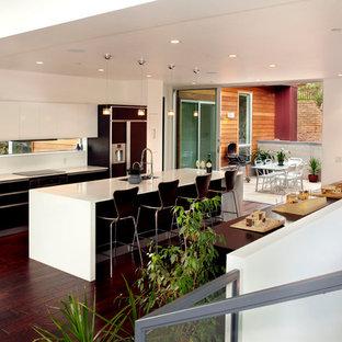 フェニックスの中サイズのモダンスタイルのおしゃれなキッチン (フラットパネル扉のキャビネット、濃色木目調キャビネット、珪岩カウンター、アンダーカウンターシンク、ガラスまたは窓のキッチンパネル、パネルと同色の調理設備、濃色無垢フローリング、赤い床) の写真