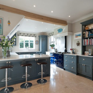 Design ideas for a large country u-shaped open plan kitchen in Kent with shaker cabinets, composite countertops, coloured appliances, blue cabinets, a breakfast bar, beige floors and white worktops.
