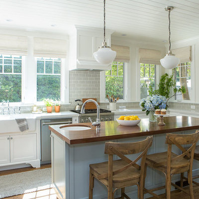 Eat-in kitchen - mid-sized coastal u-shaped medium tone wood floor and brown floor eat-in kitchen idea in Santa Barbara with a farmhouse sink, shaker cabinets, white cabinets, wood countertops, gray backsplash, subway tile backsplash, stainless steel appliances and an island