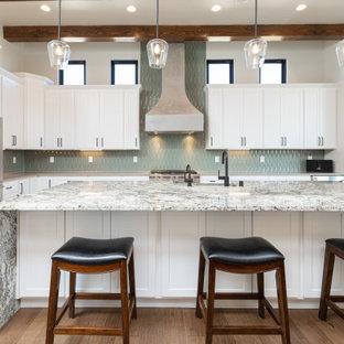 アルバカーキの広いサンタフェスタイルのおしゃれなキッチン (エプロンフロントシンク、シェーカースタイル扉のキャビネット、白いキャビネット、御影石カウンター、緑のキッチンパネル、セラミックタイルのキッチンパネル、シルバーの調理設備、無垢フローリング、茶色い床、マルチカラーのキッチンカウンター) の写真