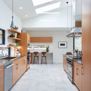 Inspiration for a large contemporary galley open plan kitchen in Portland with an undermount sink, flat-panel cabinets, medium wood cabinets, stainless steel benchtops, stainless steel appliances, porcelain floors, with island, grey floor and grey benchtop.