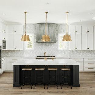 Foto på ett stort vintage vit kök, med en undermonterad diskho, skåp i shakerstil, vita skåp, bänkskiva i kvarts, grått stänkskydd, stänkskydd i marmor, rostfria vitvaror, ljust trägolv, en köksö och beiget golv