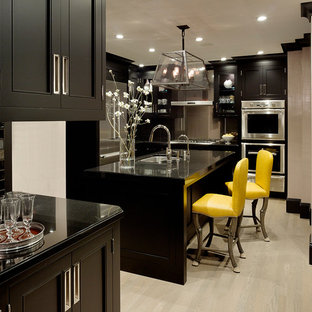 Traditional enclosed kitchen in San Francisco with a submerged sink, recessed-panel cabinets, black cabinets, black splashback, metro tiled splashback and stainless steel appliances.