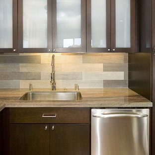 Example of a trendy kitchen design in San Francisco with granite countertops, glass-front cabinets, dark wood cabinets, gray backsplash, glass tile backsplash and stainless steel appliances