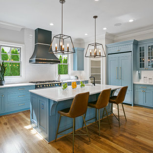 Mid-sized transitional kitchen ideas - Example of a mid-sized transitional u-shaped medium tone wood floor and brown floor kitchen design in Other with shaker cabinets, blue cabinets, white backsplash, an island, white countertops, a farmhouse sink and black appliances
