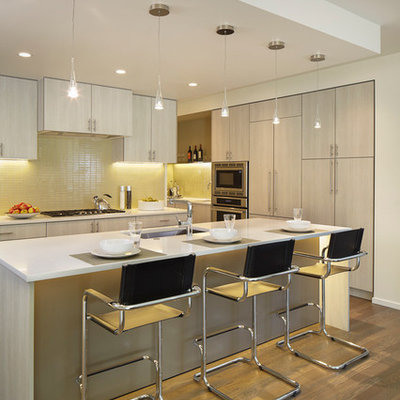 Example of a trendy kitchen design in Denver with an undermount sink, flat-panel cabinets, white cabinets, yellow backsplash and stainless steel appliances