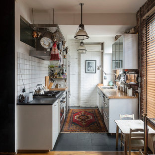 This is an example of a small eclectic galley eat-in kitchen in New York with a drop-in sink, flat-panel cabinets, white cabinets, soapstone benchtops, white splashback, ceramic splashback, stainless steel appliances, slate floors and no island.