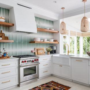 ヒューストンのトランジショナルスタイルのおしゃれなペニンシュラキッチン (エプロンフロントシンク、シェーカースタイル扉のキャビネット、白いキャビネット、グレーのキッチンパネル、シルバーの調理設備の、ベージュの床、白いキッチンカウンター) の写真