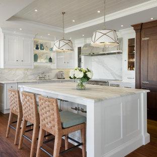 Maritim inredning av ett stort vit vitt l-kök, med en undermonterad diskho, luckor med infälld panel, vita skåp, marmorbänkskiva, mellanmörkt trägolv, en köksö, brunt golv, vitt stänkskydd, stänkskydd i sten och rostfria vitvaror