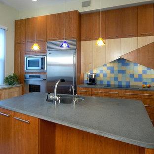 Ejemplo de cocina comedor lineal, moderna, de tamaño medio, con fregadero bajoencimera, armarios con paneles lisos, puertas de armario de madera oscura, encimera de cemento, salpicadero multicolor, salpicadero de azulejos de cemento, electrodomésticos de acero inoxidable, suelo de madera clara y una isla
