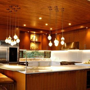 Geräumige Moderne Wohnküche in L-Form mit Unterbauwaschbecken, flächenbündigen Schrankfronten, Edelstahlfronten, Glas-Arbeitsplatte, Küchenrückwand in Weiß, Glasrückwand, Küchengeräten aus Edelstahl, Betonboden, Kücheninsel, grauem Boden und weißer Arbeitsplatte in Vancouver