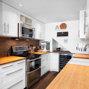 バンクーバーのトランジショナルスタイルのおしゃれなキッチン (エプロンフロントシンク、シェーカースタイル扉のキャビネット、白いキャビネット、木材カウンター、茶色いキッチンパネル、ボーダータイルのキッチンパネル、シルバーの調理設備の) の写真