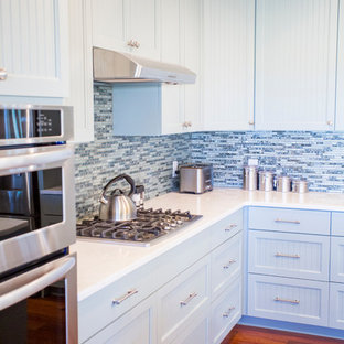 This is an example of a mid-sized beach style l-shaped eat-in kitchen in Atlanta with an undermount sink, louvered cabinets, blue cabinets, blue splashback, glass tile splashback, stainless steel appliances, medium hardwood floors and with island.