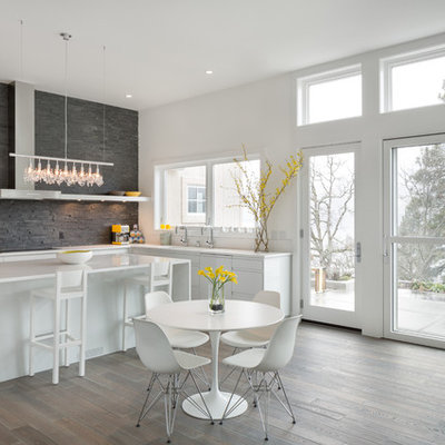 Example of a trendy eat-in kitchen design in Portland with flat-panel cabinets, white cabinets, gray backsplash and slate backsplash