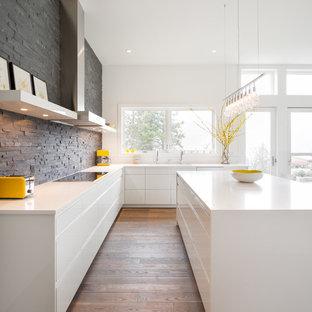 Пример оригинального дизайна интерьера: кухня в стиле модернизм с плоскими фасадами, белыми фасадами, серым фартуком, фартуком из сланца и белой столешницей