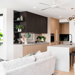 This is an example of a mid-sized contemporary l-shaped kitchen in Brisbane with an undermount sink, flat-panel cabinets, light wood cabinets, mirror splashback, stainless steel appliances, light hardwood floors, with island, beige floor and white benchtop.