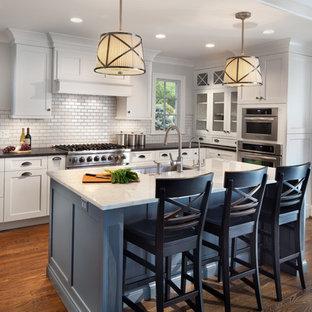 Bild på ett vintage l-kök, med en undermonterad diskho, skåp i shakerstil, vita skåp, vitt stänkskydd, rostfria vitvaror, mellanmörkt trägolv och en köksö
