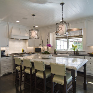 Example of a trendy l-shaped kitchen design in Charlotte with a farmhouse sink, recessed-panel cabinets, white cabinets, white backsplash, subway tile backsplash and paneled appliances