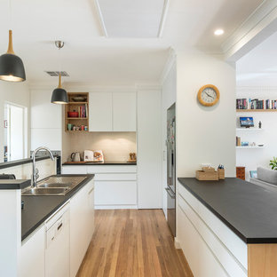 Design ideas for a mid-sized contemporary u-shaped open plan kitchen in Canberra - Queanbeyan with a double-bowl sink, flat-panel cabinets, white cabinets, beige splashback, ceramic splashback, stainless steel appliances, black benchtop, medium hardwood floors, a peninsula and brown floor.