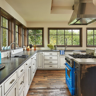 Inspiration for an expansive shabby-chic style u-shaped eat-in kitchen in Seattle with a single-bowl sink, recessed-panel cabinets, white cabinets, soapstone benchtops, medium hardwood floors, with island and brown floor.