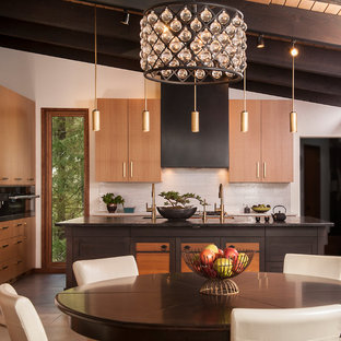 Inspiration for a large tropical single-wall eat-in kitchen in Seattle with an undermount sink, flat-panel cabinets, light wood cabinets, wood benchtops, grey splashback, porcelain floors, with island, grey floor and black benchtop.