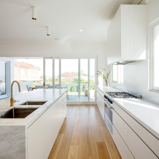 Photo of a modern galley kitchen in Sydney with an undermount sink, flat-panel cabinets, white cabinets, white splashback, stainless steel appliances, light hardwood floors, with island, beige floor and white benchtop.