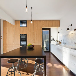 This is an example of a contemporary kitchen in Melbourne with an undermount sink, flat-panel cabinets, white cabinets, grey splashback, medium hardwood floors and with island.