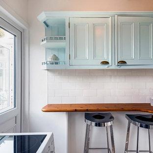 ダブリンの小さいヴィクトリアン調のおしゃれなキッチン (ドロップインシンク、インセット扉のキャビネット、ターコイズのキャビネット、木材カウンター、白いキッチンパネル、セラミックタイルのキッチンパネル、白い調理設備、ラミネートの床、アイランドなし、グレーの床、白いキッチンカウンター) の写真