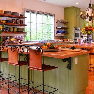 Große, Offene Mediterrane Küche in U-Form mit offenen Schränken, grünen Schränken, bunter Rückwand, Rückwand aus Mosaikfliesen, Küchengeräten aus Edelstahl, Terrakottaboden, Kücheninsel, rotem Boden, Unterbauwaschbecken und Arbeitsplatte aus Fliesen in Houston