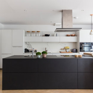 Large contemporary eat-in kitchen remodeling - Inspiration for a large contemporary galley eat-in kitchen remodel in London with an undermount sink, flat-panel cabinets, white cabinets, white backsplash and an island