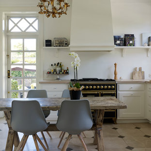 Design ideas for a small traditional u-shaped eat-in kitchen in Copenhagen with a drop-in sink, white cabinets, white splashback, black appliances, limestone floors, no island, recessed-panel cabinets and limestone benchtops.