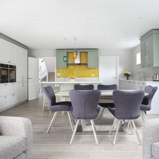 Design ideas for a contemporary u-shaped open plan kitchen in Buckinghamshire with shaker cabinets, green cabinets, yellow splashback, glass sheet splashback, stainless steel appliances, with island, grey floor and white benchtop.