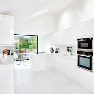 Inspiration for a contemporary kitchen/diner in Devon with flat-panel cabinets, white cabinets, white splashback and marble flooring.