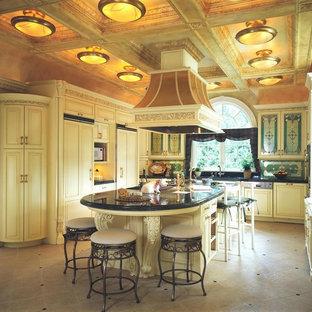 Ejemplo de cocina en L, clásica, de tamaño medio, cerrada, con fregadero bajoencimera, armarios con rebordes decorativos, puertas de armario blancas, encimera de granito, salpicadero multicolor, salpicadero de azulejos de vidrio, electrodomésticos de acero inoxidable, suelo de baldosas de porcelana, una isla y suelo beige