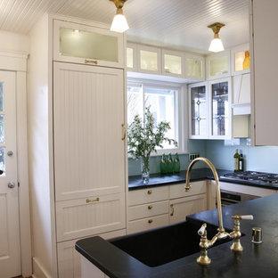 Inredning av ett klassiskt u-kök, med en rustik diskho, vita skåp, bänkskiva i täljsten, blått stänkskydd, glaspanel som stänkskydd och integrerade vitvaror