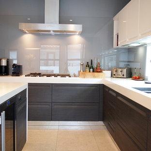 ロサンゼルスの大きいコンテンポラリースタイルのおしゃれなキッチン (ダブルシンク、フラットパネル扉のキャビネット、ターコイズのキャビネット、人工大理石カウンター、白いキッチンパネル、石スラブのキッチンパネル、シルバーの調理設備の、セラミックタイルの床、白い床) の写真