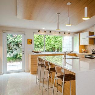 50 tals inredning av ett l-kök, med släta luckor, skåp i ljust trä, grått stänkskydd, stänkskydd i glaskakel, betonggolv, en köksö, en undermonterad diskho och vitt golv