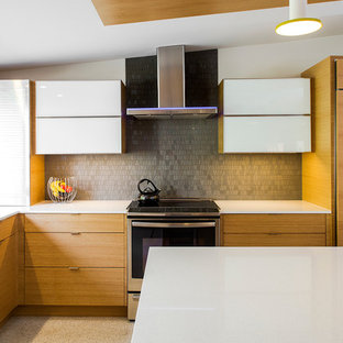 Photo of a midcentury l-shaped kitchen in Tampa with flat-panel cabinets, light wood cabinets, grey splashback, glass tile splashback, concrete floors and with island.