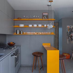 Imagen de cocina lineal, contemporánea, pequeña, abierta, con fregadero bajoencimera, armarios con paneles lisos, electrodomésticos de acero inoxidable, suelo de cemento, una isla, puertas de armario grises, encimera de acrílico, salpicadero metalizado, suelo gris y encimeras grises