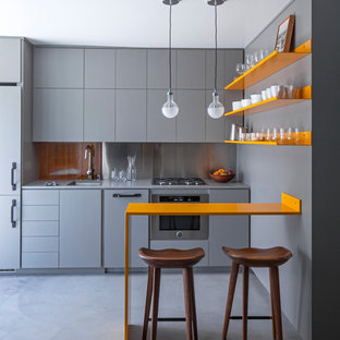 Imagen de cocina lineal, contemporánea, pequeña, abierta, con fregadero bajoencimera, armarios con paneles lisos, suelo de cemento, puertas de armario grises, salpicadero metalizado, electrodomésticos con paneles, encimera de acrílico, suelo gris y encimeras grises