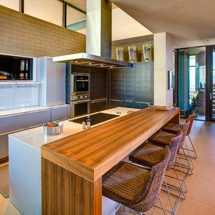 Ispirazione per una cucina minimalista di medie dimensioni con ante lisce, ante grigie, elettrodomestici in acciaio inossidabile, pavimento in gres porcellanato, isola e pavimento beige
