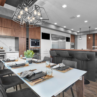 Photo of a mid-sized contemporary kitchen in Edmonton with an undermount sink, louvered cabinets, white cabinets, wood benchtops, grey splashback, porcelain splashback, stainless steel appliances, medium hardwood floors, brown floor and brown benchtop.