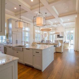 Новые идеи обустройства дома: кухня-гостиная в морском стиле с раковиной в стиле кантри, фасадами в стиле шейкер, белыми фасадами, темным паркетным полом и островом