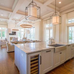 Inspiration pour une cuisine ouverte marine en L avec un évier de ferme, un placard à porte shaker, des portes de placard blanches, un sol en bois foncé et un îlot central.