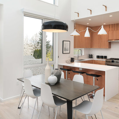 Example of a trendy u-shaped light wood floor and beige floor eat-in kitchen design in Portland with an undermount sink, flat-panel cabinets, medium tone wood cabinets, white backsplash, stainless steel appliances, a peninsula and white countertops