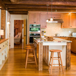 Geschlossene, Mittelgroße Country Küche in L-Form mit Unterbauwaschbecken, Schrankfronten im Shaker-Stil, hellbraunen Holzschränken, Onyx-Arbeitsplatte, Küchenrückwand in Beige, Rückwand aus Mosaikfliesen, schwarzen Elektrogeräten, braunem Holzboden und Kücheninsel in Burlington