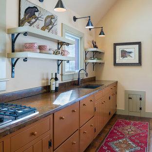 Farmhouse open concept kitchen designs - Open concept kitchen - cottage single-wall open concept kitchen idea in Burlington with shaker cabinets, orange cabinets and concrete countertops