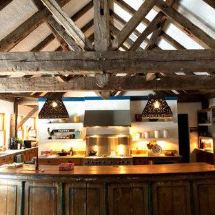 他の地域の巨大なサンタフェスタイルのおしゃれなキッチン (インセット扉のキャビネット、ヴィンテージ仕上げキャビネット、木材カウンター、メタルタイルのキッチンパネル、レンガの床、赤い床、茶色いキッチンカウンター) の写真