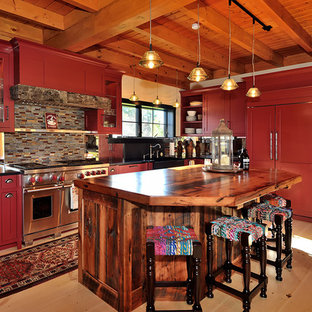 This is an example of an expansive rustic u-shaped kitchen/diner in New York with red cabinets, recessed-panel cabinets, a belfast sink, granite worktops, multi-coloured splashback, mosaic tiled splashback, stainless steel appliances, light hardwood flooring and an island.