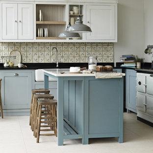 チェシャーの大きいカントリー風おしゃれなキッチン (エプロンフロントシンク、シェーカースタイル扉のキャビネット、青いキャビネット、珪岩カウンター、テラコッタタイルのキッチンパネル、白い調理設備、ライムストーンの床) の写真